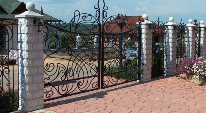 Кованый забор с колпаками на столбах из бетона